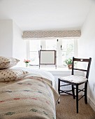 Black wooden chair next to bed and swivelling vanity mirror on windowsill in bedroom