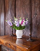 White jug of summer flowers on antique writing desk against rustic board wall