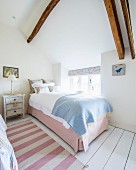 Pink and white striped runner on white wooden floor and single bed next to window in rustic bedroom
