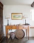 Table lamps on simple console table with drawers above vases and wicker basket on stone floor