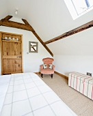 Double bed and dainty armchair in corner below exposed wooden roof beams