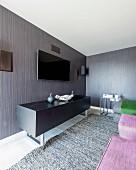 Black sideboard below flatscreen TV on grey and brown striped wallpaper in modern interior
