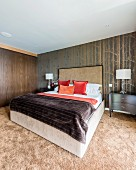 Doppelbett mit hohem Kopfteil, vor tapezierter Wand mit Birkenwaldmotiv im Schlafzimmer mit flauschigem Teppichboden