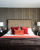 Scatter cushions arranged on double bed with tall headboard against wallpaper with pattern of birch trunks