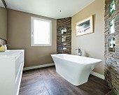 Free-standing bathtub on large floor tiles in modern bathroom with sections of stone wall
