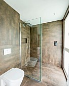 Toilet next to glazed, floor-level shower area in modern bathroom with large brown tiles on walls and floor