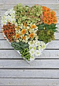 Hand-made, heart-shaped arrangement of chrysanthemums, hydrangeas and berries on wooden surface