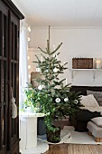 Schlicht geschmückter Weihnachtsbaum neben Kabelrolle und Sessel