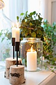 Lit candles in birch stump holders and in preserving jar