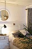 Winterliches Schlafzimmer mit Felldecke und warmem Licht, Tannenbaum im Anschnitt