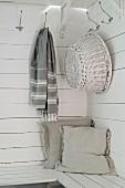 Wooden bench in corner below basket on hook on white board wall