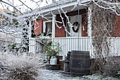 Backsteinhaus mit Veranda im winterlichen Garten mit Raureif