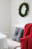 Grey felt cushion and red and white patterned blanket on white-painted bench below Christmas wreath on wall