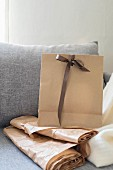 Hellbraune Papiertüte mit Schleife und Papierrolle auf Couch