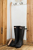 Black Wellington boots and long-handled brush in corner
