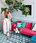 Young woman in interior with hot pink sofa, glass table, tiled floor and lemon tree
