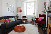 Colourful scatter cushions on grey sofa and red velvet armchair in living room