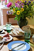 Summer bouquet, bread and salami on table in kitchen-dining room