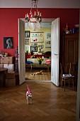 Blick durch geöffnete Flügeltüren in Wohnraum mit Sofa und Bilderwand in Altbauwohnung