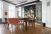 Antique chairs and wooden table in dining room with modern quilt on wall