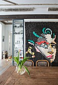 Portrait on modern quilt hung on wall behind wooden dining table