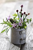 Freshly-picked, flowering herbs in metal mug