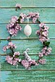 Kranz aus rosa Kirschblüten mit Osterei und silbernem Osterhasen an einer Holzwand