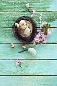 Easter nest with Easter eggs, quail's eggs and sprig of cherry blossom on wooden surface