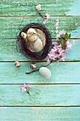 Osternest mit Ostereiern, Wachteleiern und Kirschblütenzweig auf Holzuntergrund
