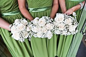 Three bridesmaids holding posies of white roses