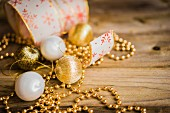 Goldene Kugeln, Dekoketten und Geschenkband auf Holzuntergrund