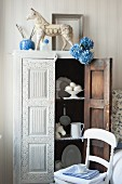 Horse figurine on top of antique, Indian crockery cupboard in dining room in shades of blue and white