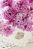 Pink hyacinth flowers, lace doily and rhinestone brooch
