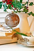 Christmas bauble with forest motif hanging from holly in jug next to stack of books and teacup