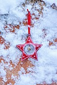 Red, festive star with artificial snow on cross-grained wood
