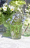 Arrangement of various spring flowers in glass vessels