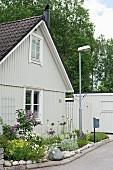 Hellgraues Holzhaus mit Giebeldach, blühende Blumen im Vorgarten