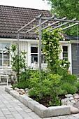 Trellis pergola above flowerbed on terrace adjoining house