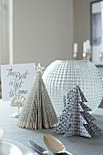 Festive Christmas tree ornaments made from folded black and white paper and book pages on table