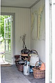 Wicker baskets and gardening utensils on floor of hall with white wood panelling and open garden door in background