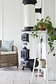 House plant on plant stand next to vintage stove and wicker chair