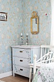 Painted chest of drawers in corner below mirror with ornate gilt frame on floral wallpaper
