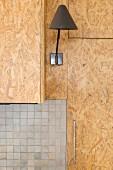 Schlichte Wandleuchte an Küchenfront aus OSB-PLatte