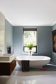Free-standing bathtub, mid-grey walls and section of floor and polished white floor tiles in elegant bathroom