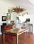 Kugelvase auf Holztisch unter von Decke abgehängtem Kunstobjekt aus Holzstäben, im Hintergrund offene Küche mit Theke