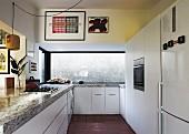 Moderne Einbauküche in Weiss, auf Unterschränken massive Steinplatte, im Hintergrund breites Fenster mit Blick auf Mauer