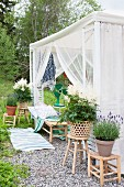 Romantic garden pavilion with airy fabric curtains and potted plants