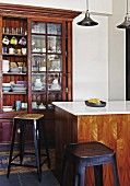 Retro bar stools around counter in front of crockery in antique glass-fronted cabinet