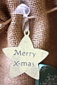 Star-shaped gift tag reading 'Merry X-mas' on hessian bag
