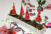 Hand-crafted, festive table decoration with garlands, paper Christmas trees & pine cones